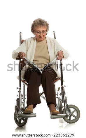 80 Year Old Elderly Senior Woman Sit in Wheelchaire Reading Magazine Isolated on White Background - stock photo
