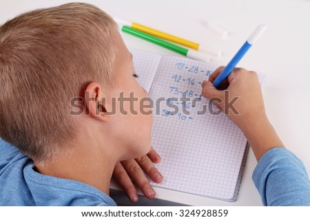 8 year old elementary school age boy does math homework. Kids,  education concept - stock photo