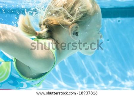 4 year old girl enjoys an underwater swim. - stock photo