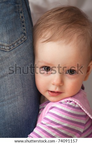 1 year old girl hugging man's leg. She's looking at camera. Focused on girl - stock photo