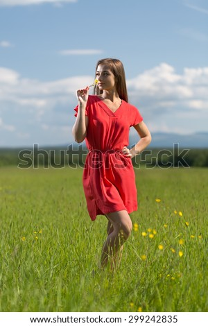 20 year-old girl in red dress sniffing a yellow flower in a field on a sunny day - stock photo
