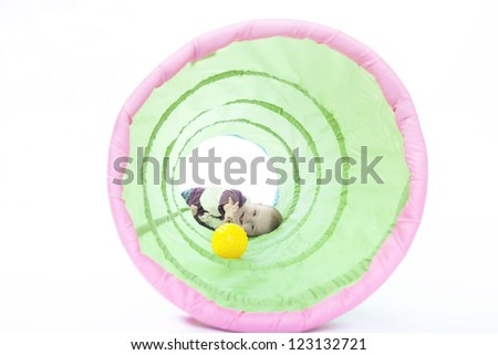 1 year old girl playing inside a toy tunnel. studio shot,isolated on white