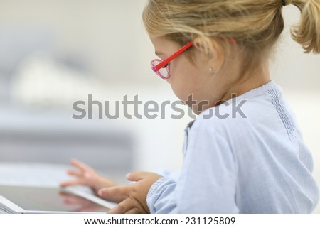 4-year-old girl playing with digital tablet - stock photo