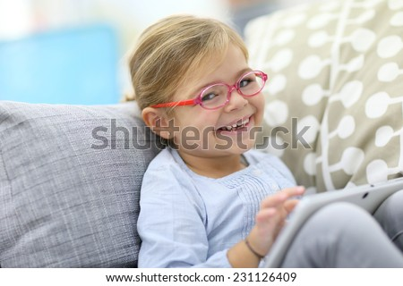 4-year-old girl playing with tablet at home - stock photo