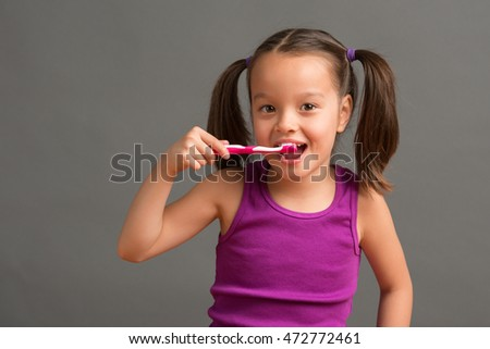 5 year old girl smiling while brushing her teeth.
