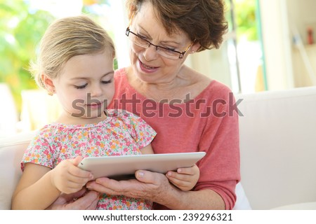 4-year-old girl with grandma playing on digital tablet - stock photo