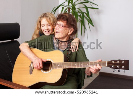 90 year old grandmother to play the guitar. Elderly woman with child at home. Mature female hobbies. Generation