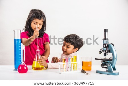 4 year old indian boy and girl doing science experiment, science Education. asian kids and science experiments, chemistry experiment, indian kids and science experiments, indian kids and science lab   - stock photo