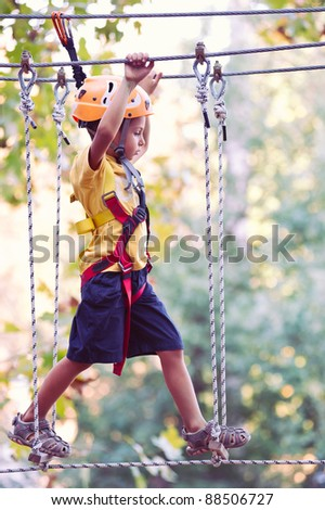 6 year old Kid climbing trees in Dolomites, Italy. - stock photo