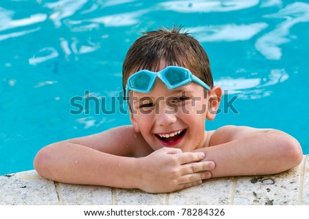 5 year old kid laughing in a swimming pool. - stock photo