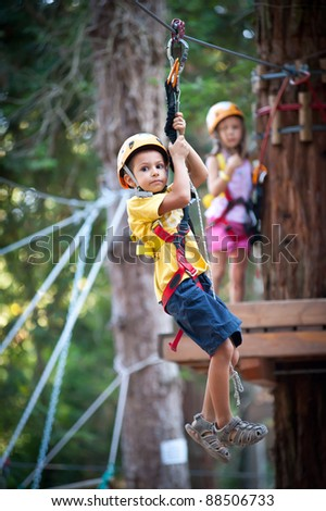 6 year old Kids climbing trees in Dolomites, Italy. - stock photo