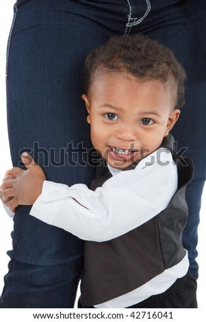 2 year old little African American boy holding Mom's leg standing - stock photo