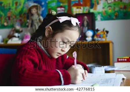 8-year old little asian girl doing homework - stock photo