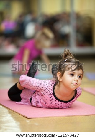 5 year old little girl doing sports exercises on the mat (stretching) - stock photo