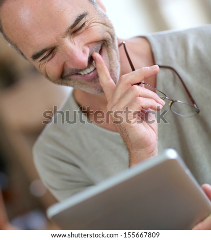 50-year-old man using digital tablet - stock photo