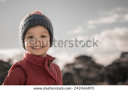 4 year old mixed race Asian Caucasian boy wearing winter clothes and looking at the camera - stock photo