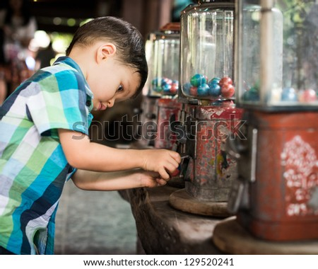 2 year old mixed race boy eagerly takes the toy he bought from the vintage vending machine at Bang Nam Pheung market in Bangkok, Thailand - stock photo