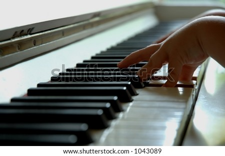 4 year old playing the piano. - stock photo