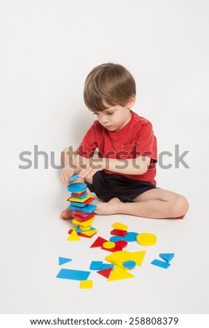 3 year old preschool boy stacking shape blocks - stock photo