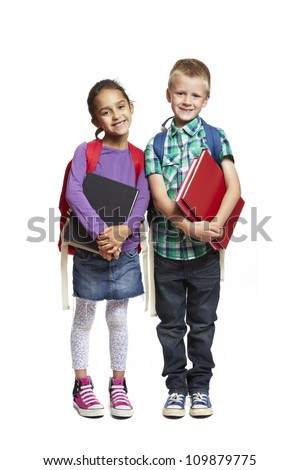 8 year old school boy and girl with backpacks holding books smiling on white background - stock photo