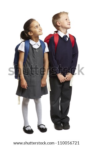 8 year old school boy and girl with backpacks looking up on white background - stock photo