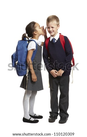 8 year old school girl with backpack whispering in boys ear smiling on white background - stock photo