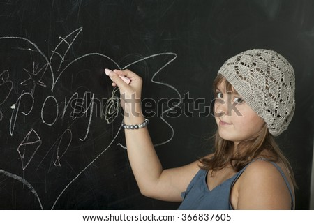 12-year-old schoolgirl standing near blackboard with chalk in hand - stock photo