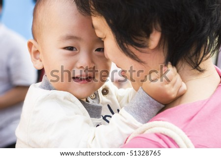 2-year old toddler in young asian mother's arms. - stock photo