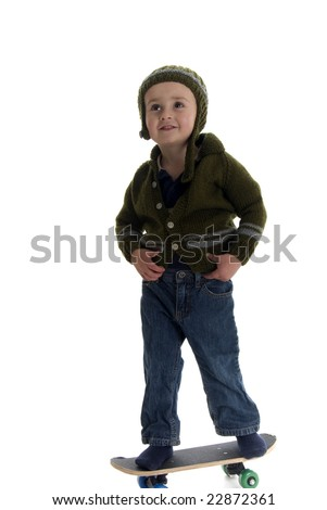 2 year old with sweater and hat stands on skateboard