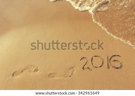 2016 year written and footprint on sandy beach sea. Concept come new year. Toned image.  - stock photo