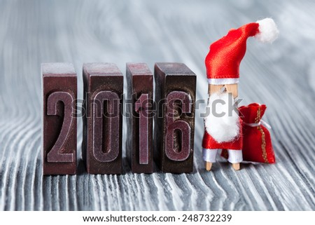 2016 year. written with colored vintage letterpress. Christmas concept - clothespin Santa Claus with a bag of gifts. Father frost. Papa Noel. (soft focus, vintage wood background). - stock photo