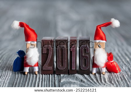 2016 year written with colored vintage letterpress. Christmas concept - clothespin two Santa Claus with a bags of gifts. Father frost. Papa Noel. (soft focus, vintage wood background). - stock photo