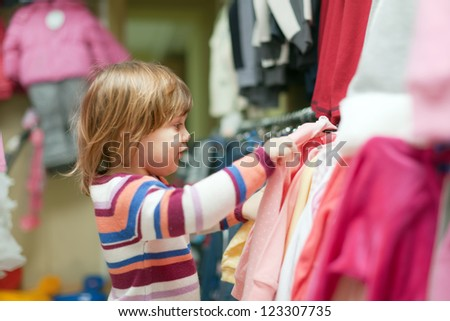 2 years baby girl  chooses clothes at fashionable shop