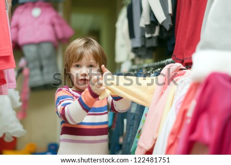 2 years baby girl looking at wear in clothes shop