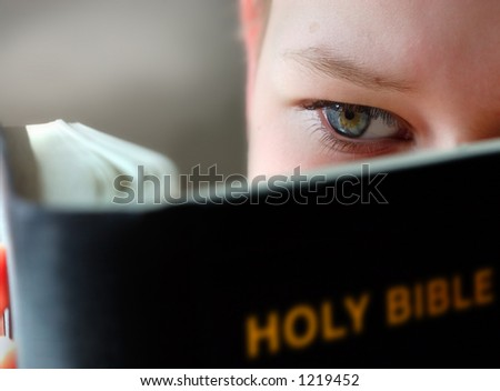 10-11 years boy reading the holy bible - stock photo