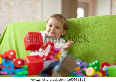 3 years child plays with toys in home interior - stock photo