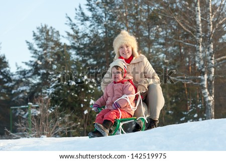 2 years child sliding downhill on sledge in winter - stock photo