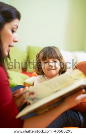 2-3 years girl listening to fairy tale in kindergarten. Vertical shape, copy space - stock photo
