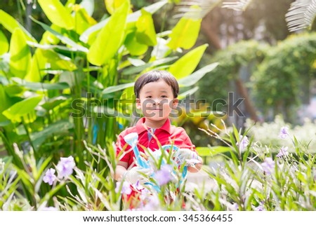5 years old asian boy in his flower garden - kids and family. Portrait of a boy working in the garden in holiday