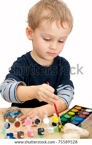 3 years old baby boy painting the stones with watercolor - over white background - stock photo