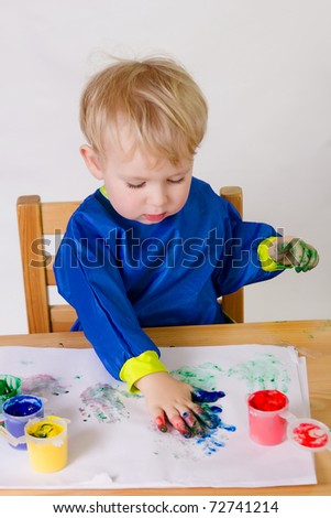 2 years old baby boy paintings without paintbrush. - stock photo