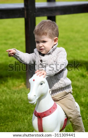 2 years old Baby boy playing with horse on playground  - stock photo