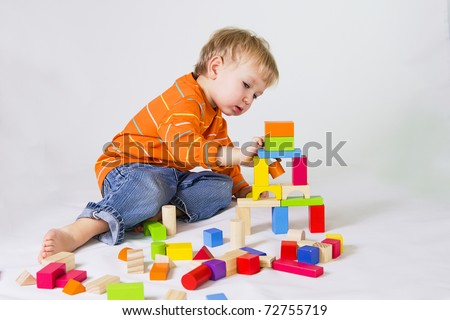 2 years old baby boy playing with wooden blocks. - stock photo