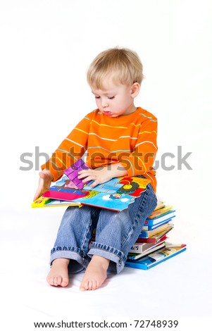 2 years old baby boy reading pop-up books. - stock photo