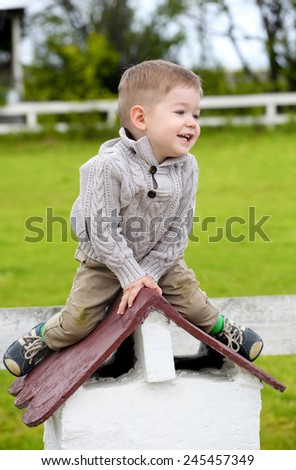 2 years old baby boy sitting on the little rooftop - stock photo