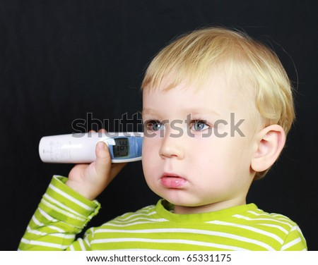 2 years old baby boy waits for a digital thermometer to determine his temperature. - stock photo