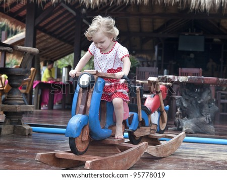 3 years old baby girl playing with rocking horse - stock photo