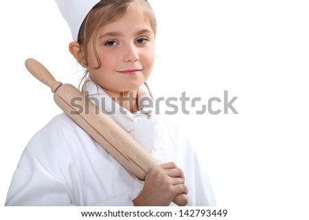 10 years old blonde girl dressed in pastry cooker and taking a rolling pin
