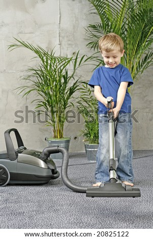 4-5 years old boy cleaning carper - housework - stock photo