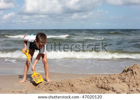 7 years old boy digging in the sand - kids - stock photo